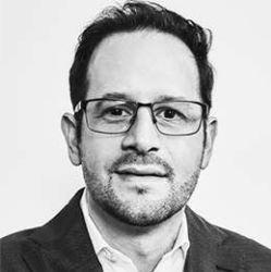 Imagen en blanco y negro de un hombre con lentes y traje  Descripción generada automáticamente